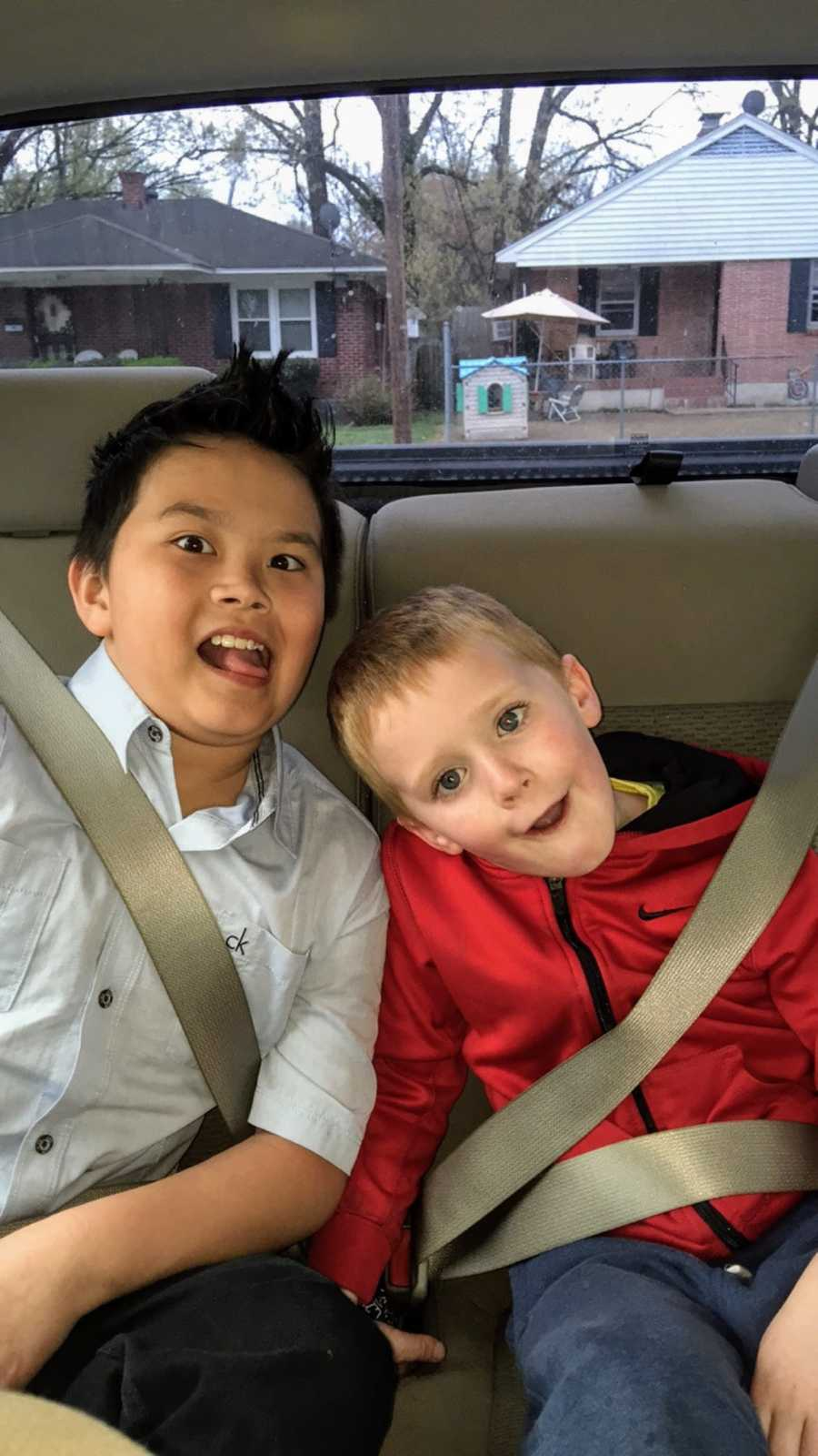 A pair of young brothers sit in the back of their mom's car