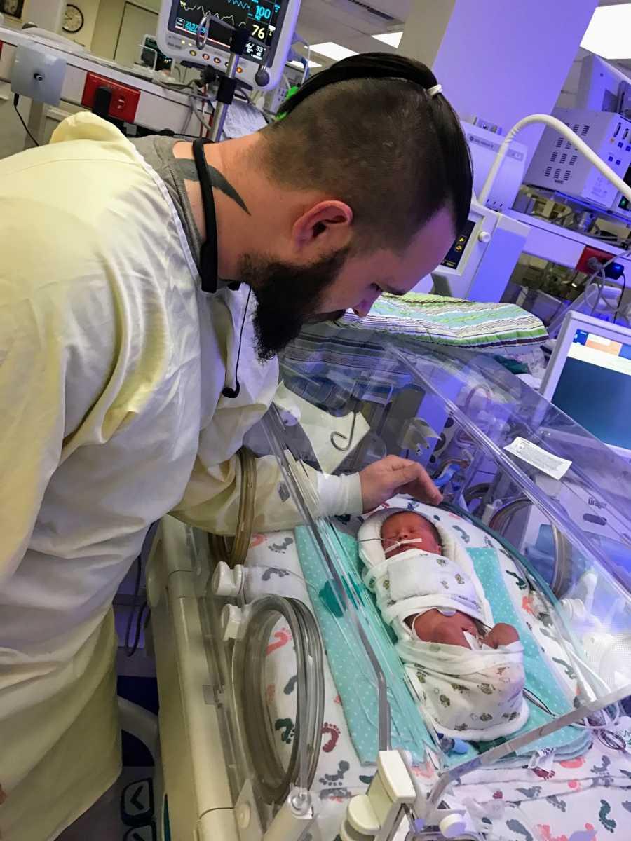 A father checks on his newborn son in the NICU