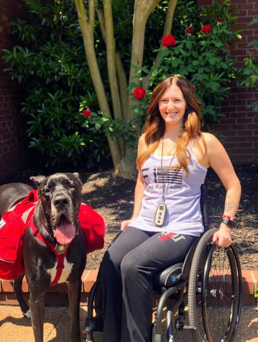 A disabled woman sitting in her wheelchair next to her service dog