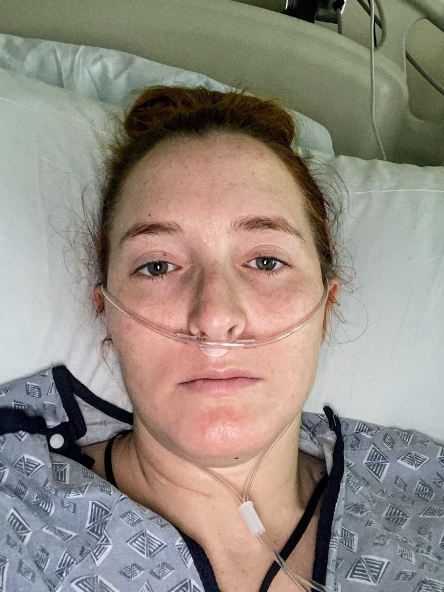A woman lies in a hospital bed with an oxygen tube