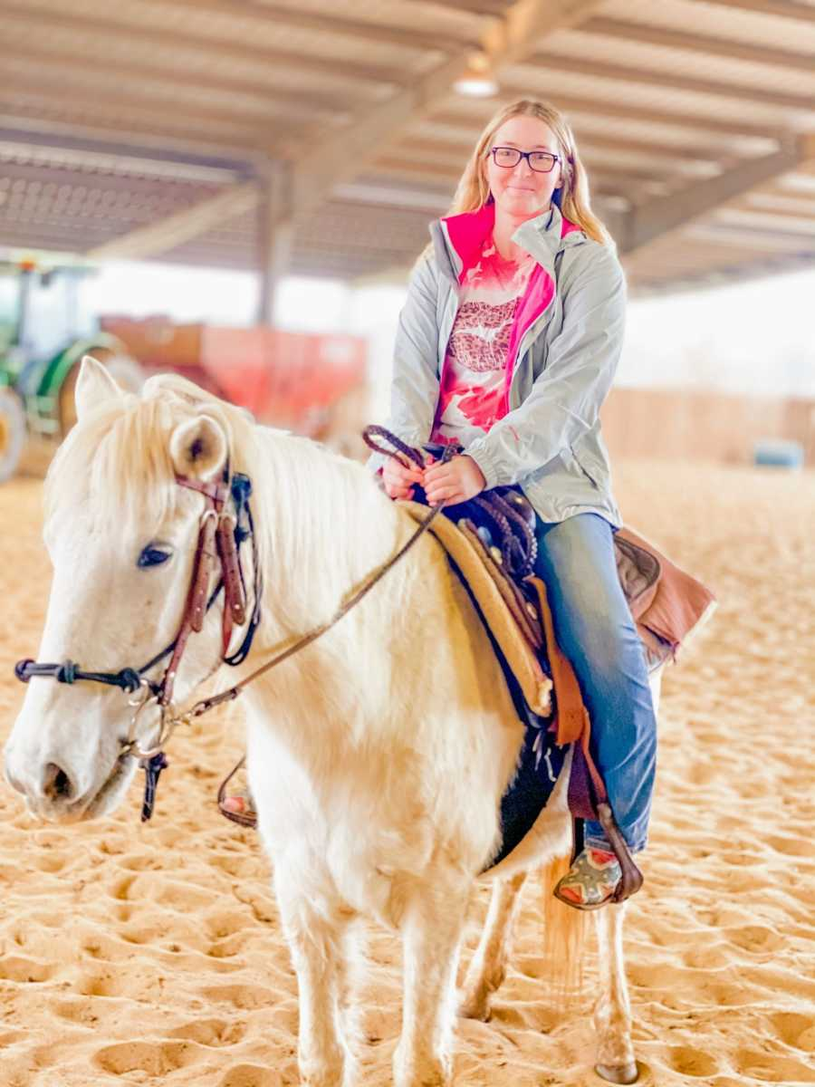 A disabled woman rides a white horse