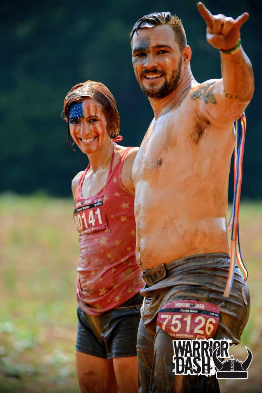 A woman with American flag face paint and her husband stand in muddy clothes