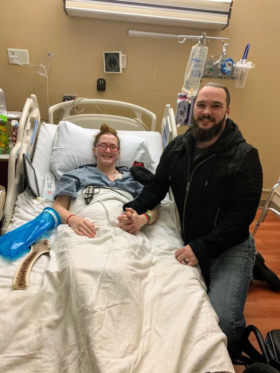 A disabled woman sits in a hospital bed while her husband holds her hand