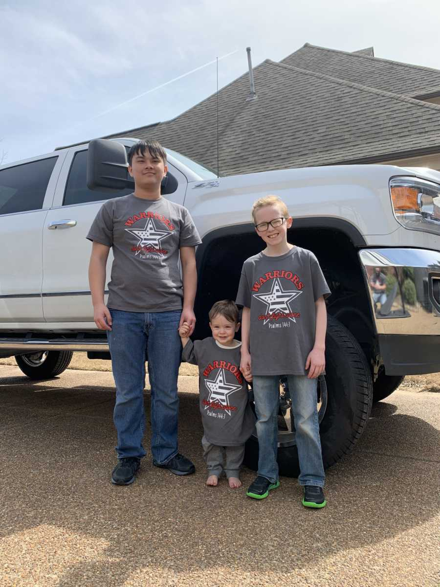 Three brothers stand together next to a truck