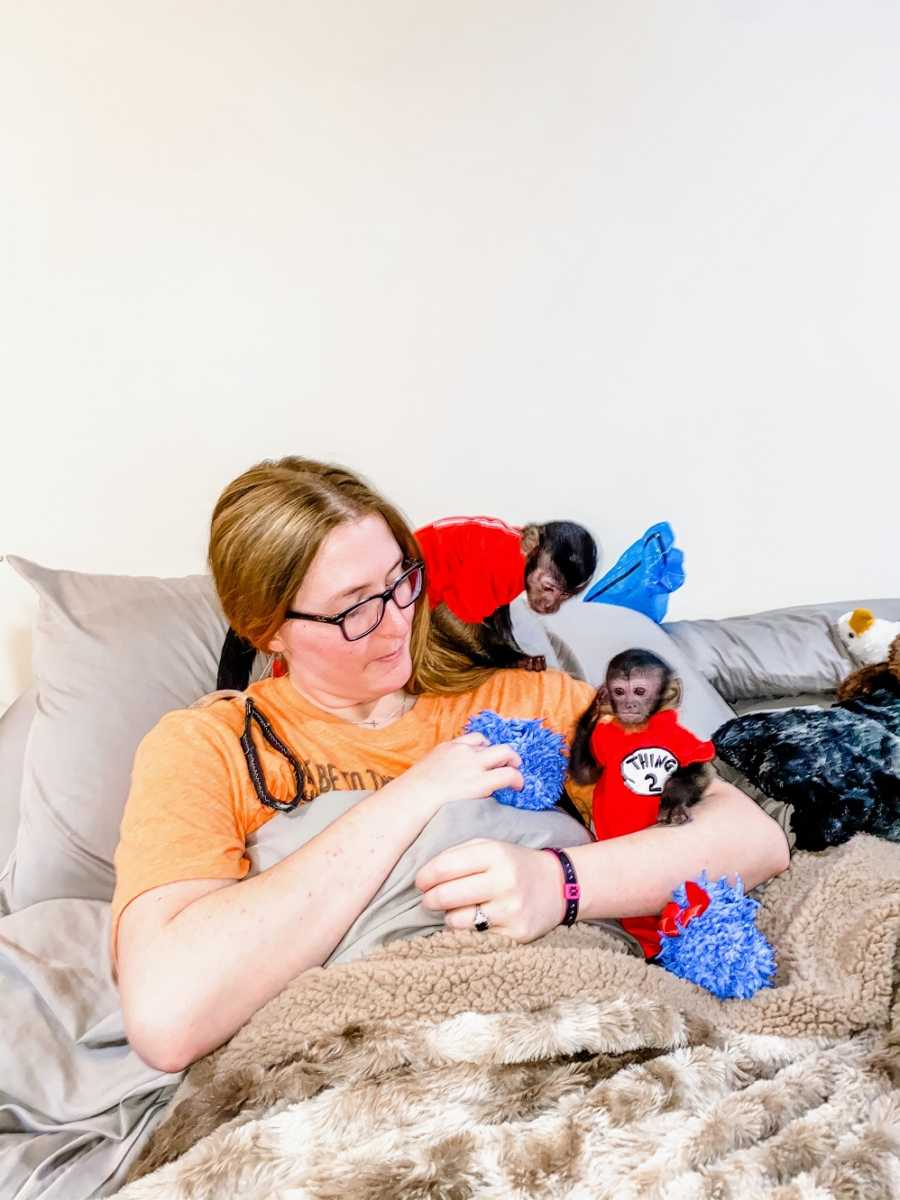 A disabled woman and her two primates sit on a bed