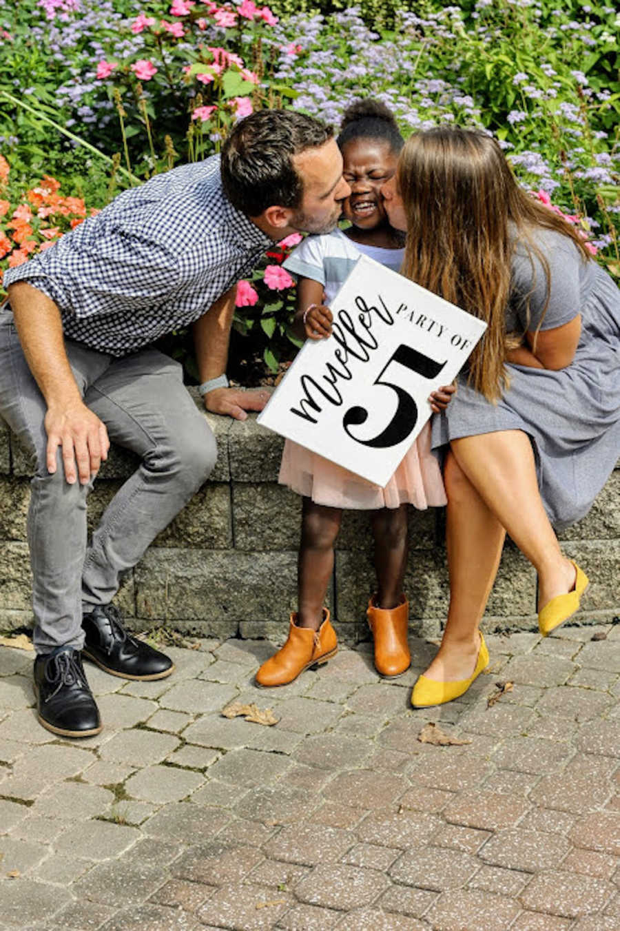 Mother and father kissing newly adopted daughter
