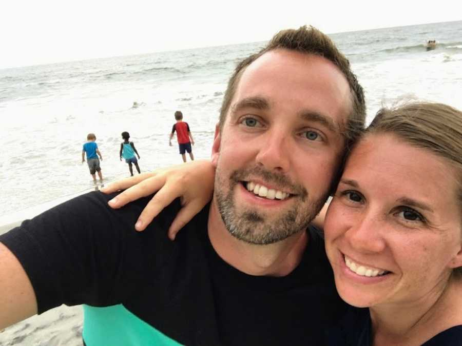 Husband and wife taking smiling selfie at beach