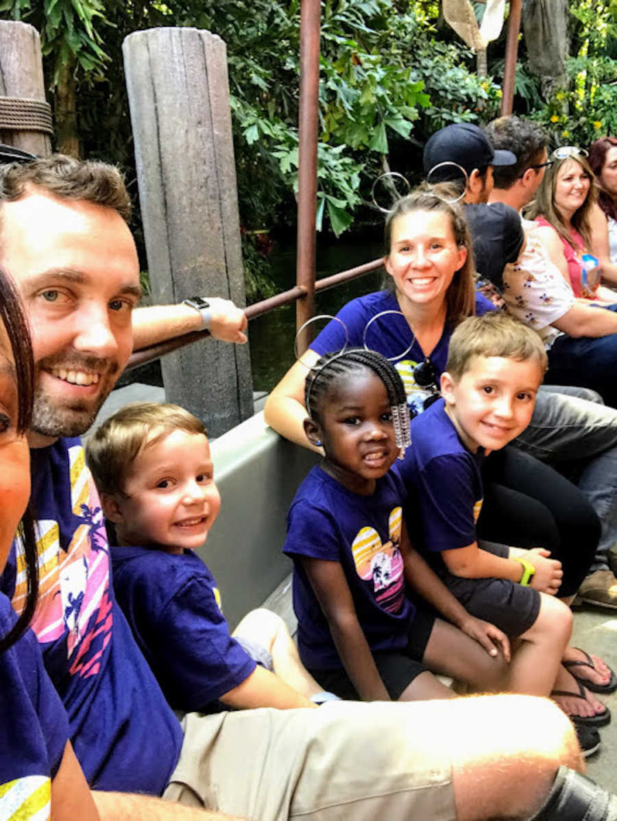 Family of five sitting in line for a ride at Disney