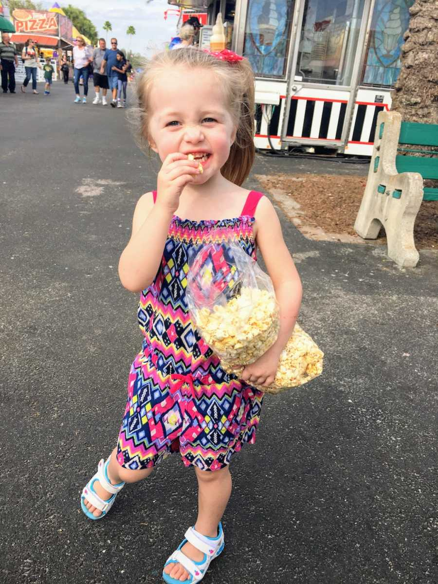 Young girl standing outside holding a bag of popcorn