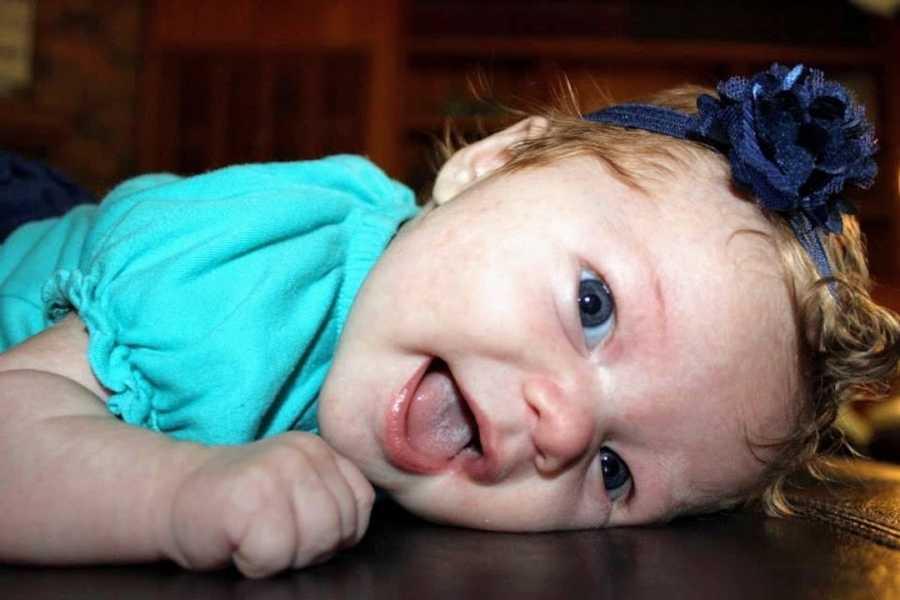 Baby girl wearing blue shirt lying on floor