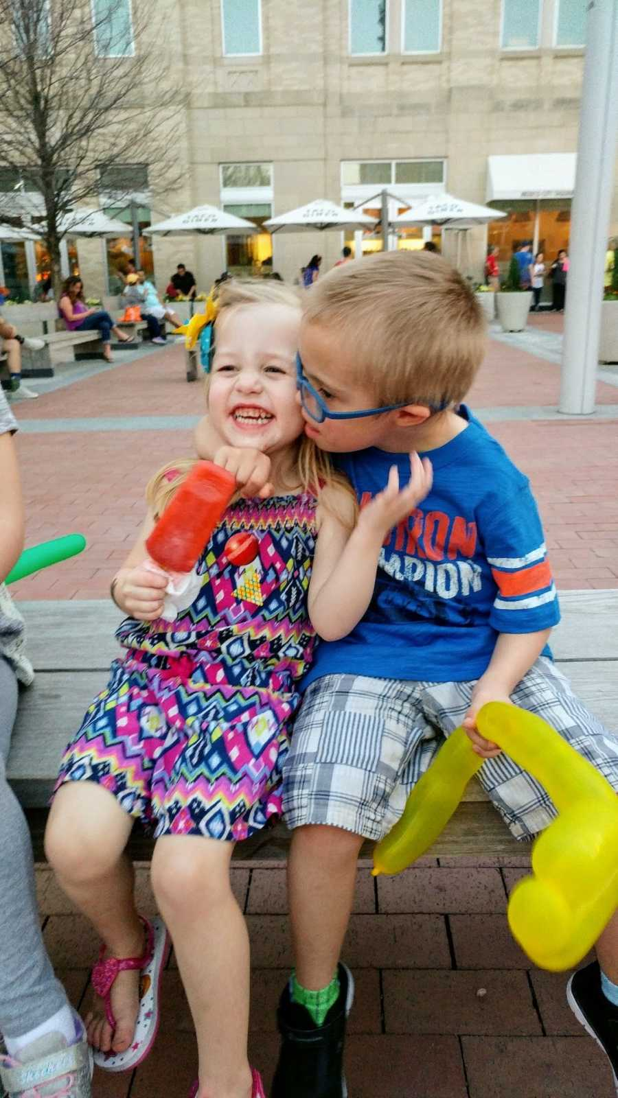 Sister and brother sitting outside with brother kissing sister on the cheek