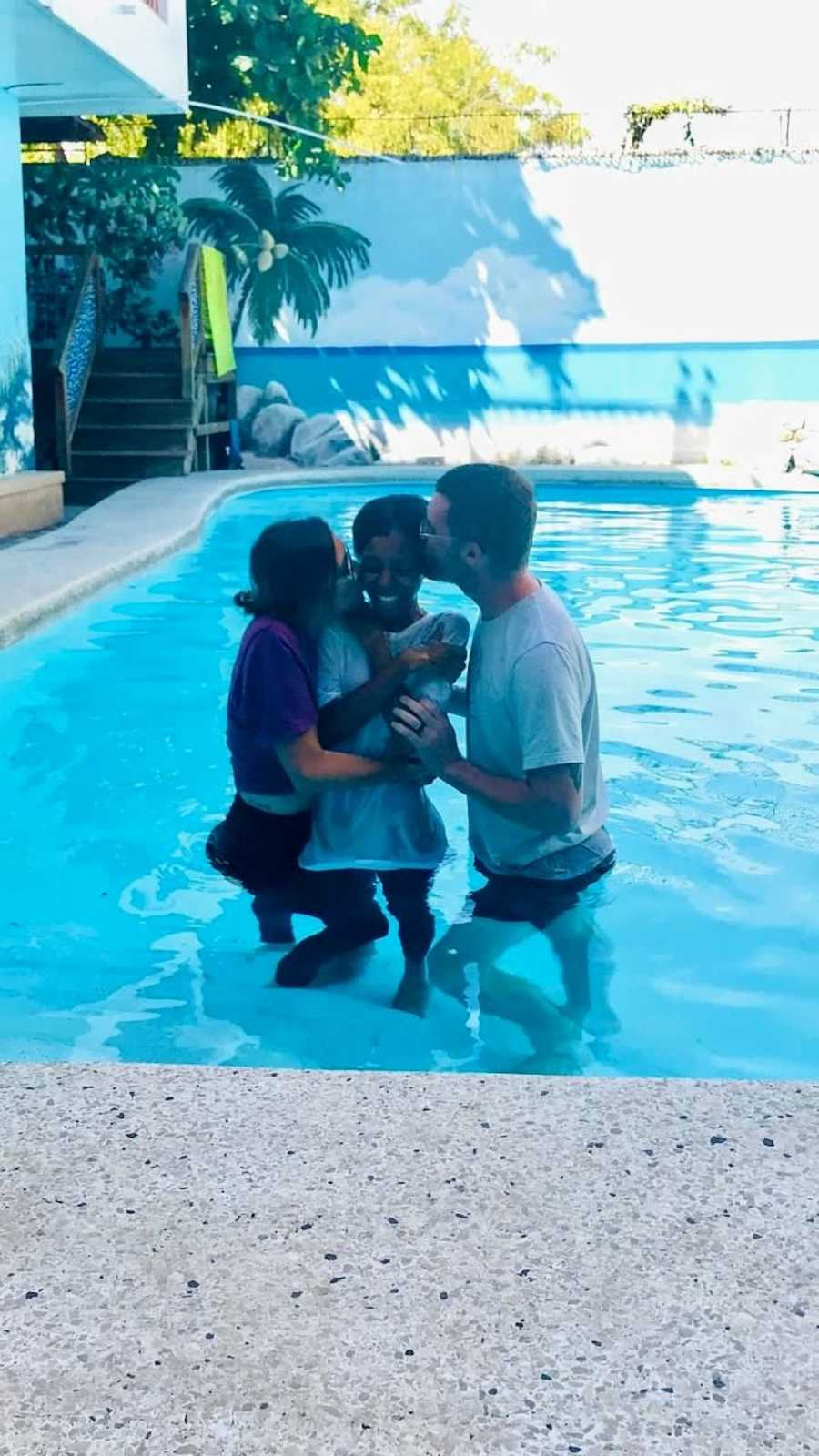Parents baptising daughter in outside pool