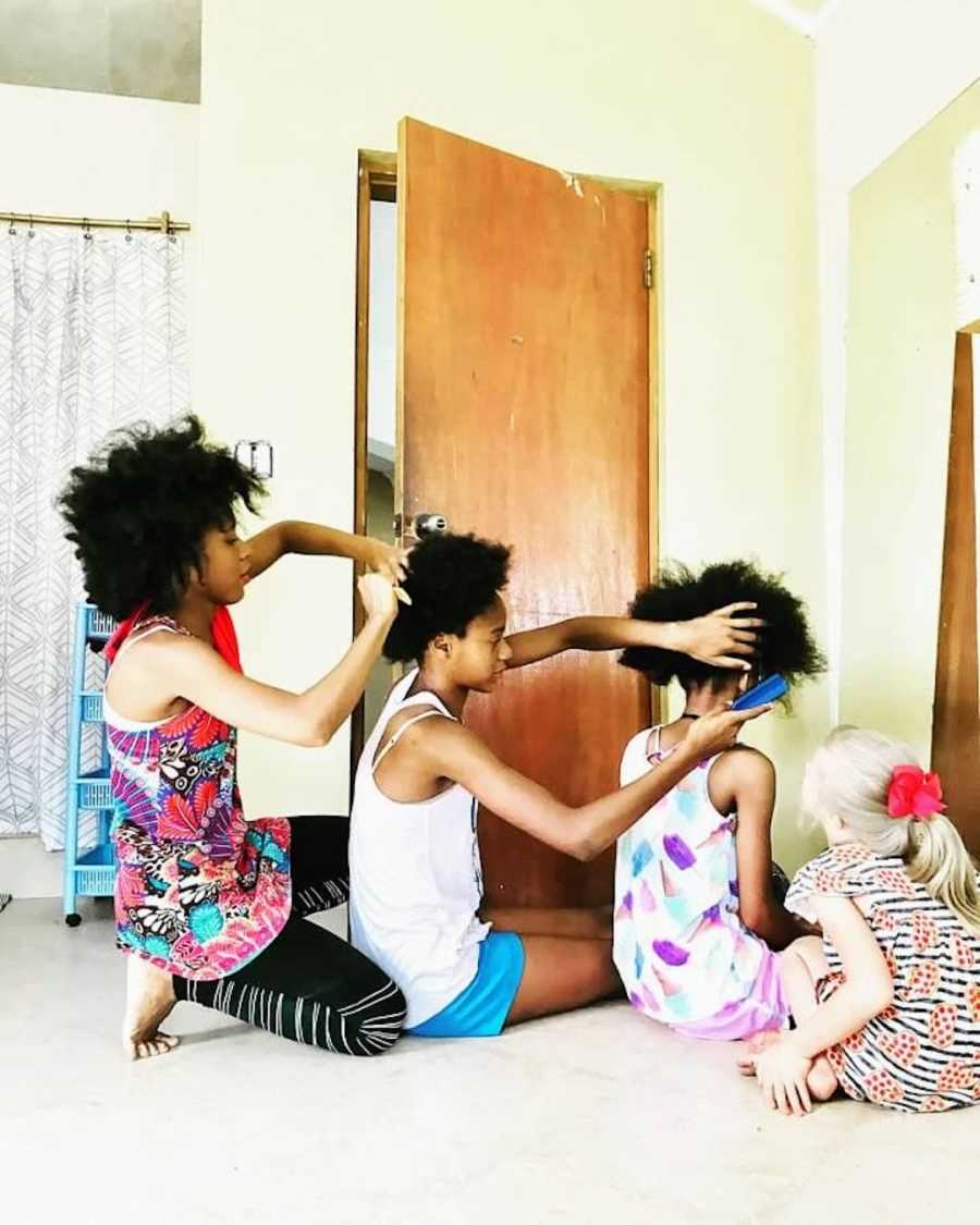 4 siblings doing each other's hair on the floor