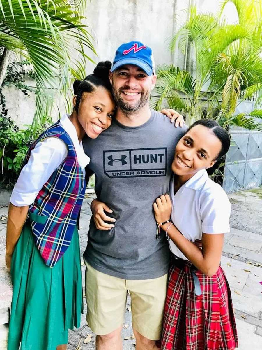 Man smiling with two daughters outside with palm trees
