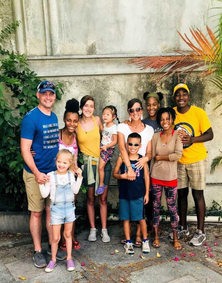 Family of 10 standing outside smiling