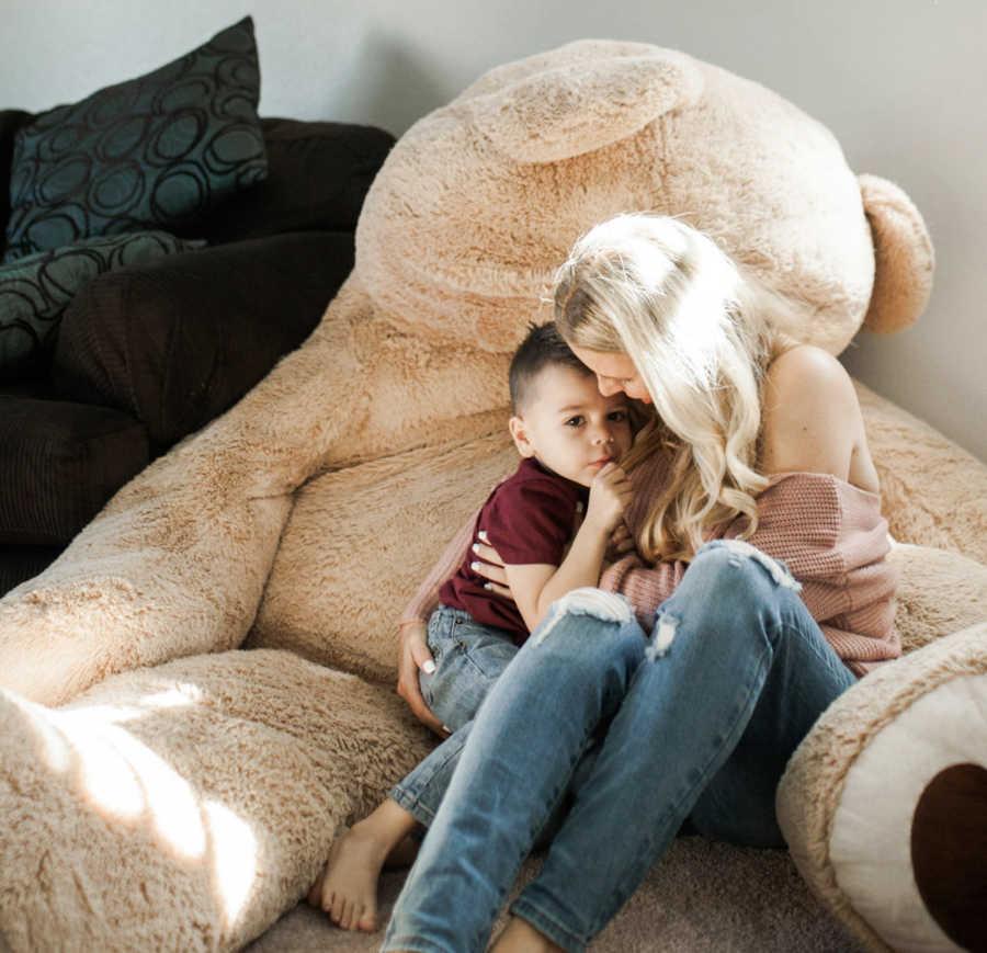 mom holding baby on stuffed animal