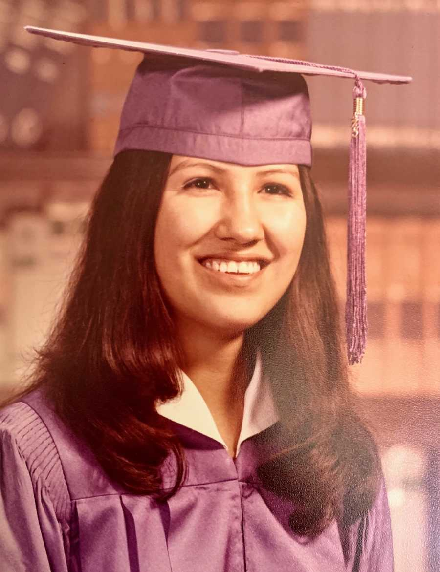 Young woman smiling wearing graduation cap and gown
