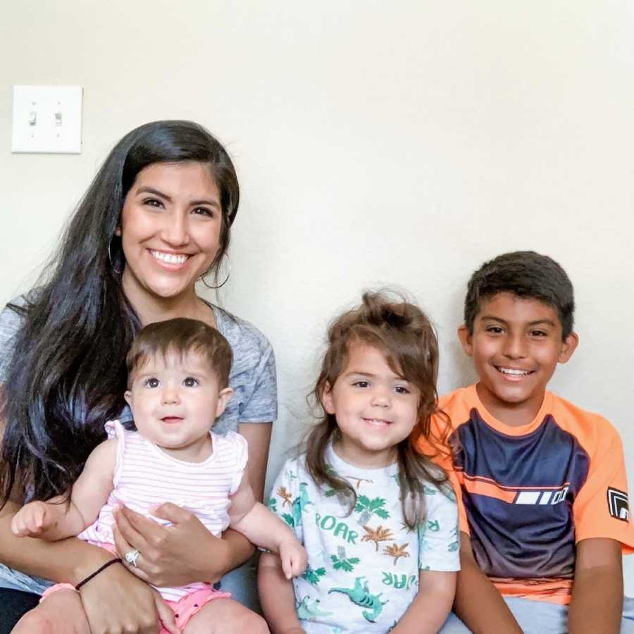 Mother sitting in front of white wall with three children and smiling