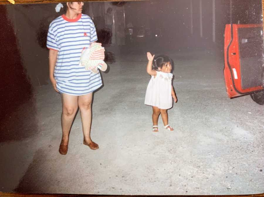 Mother and daughter standing in a garage with a red car