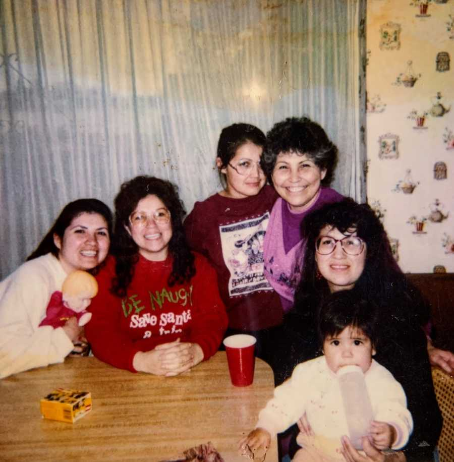 Family photo at a kitchen table with five women and a toddler