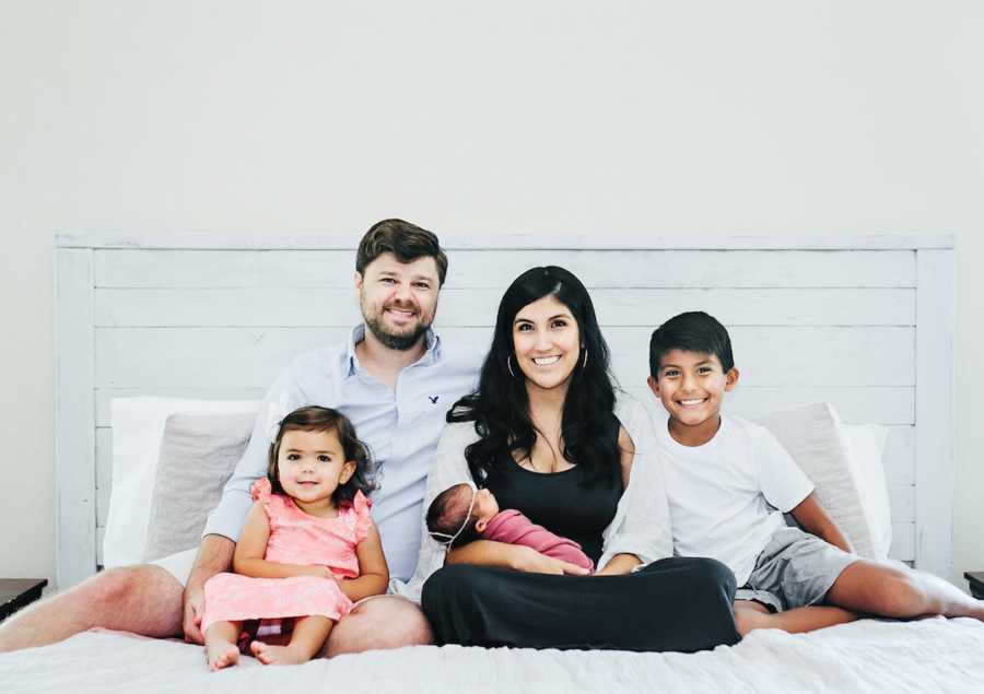 Family of five sitting on white bed and smiling