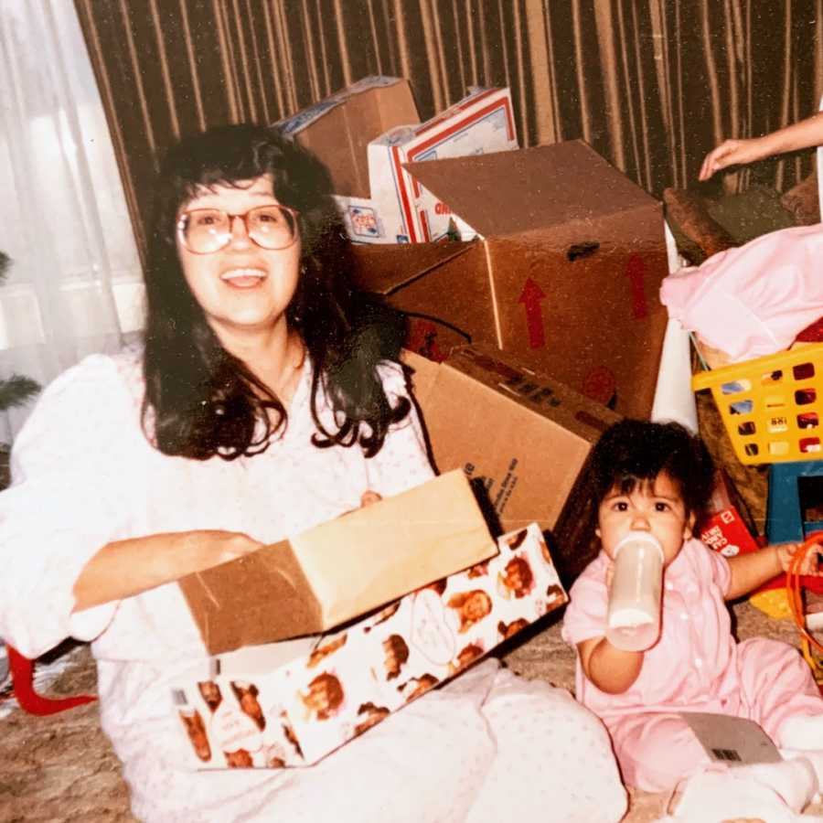 Mother and daughter sitting on the floor with boxes surrounding them