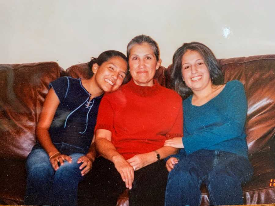 Mother sitting on leather couch with two daughters