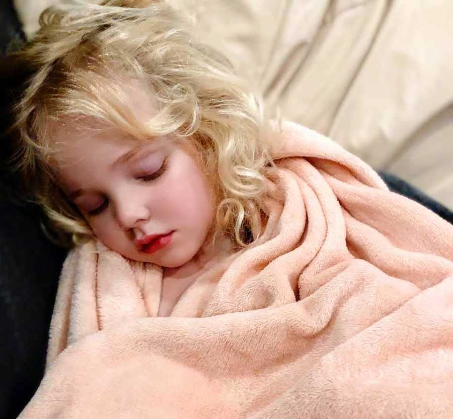 young girl sleeping in a pink blanket