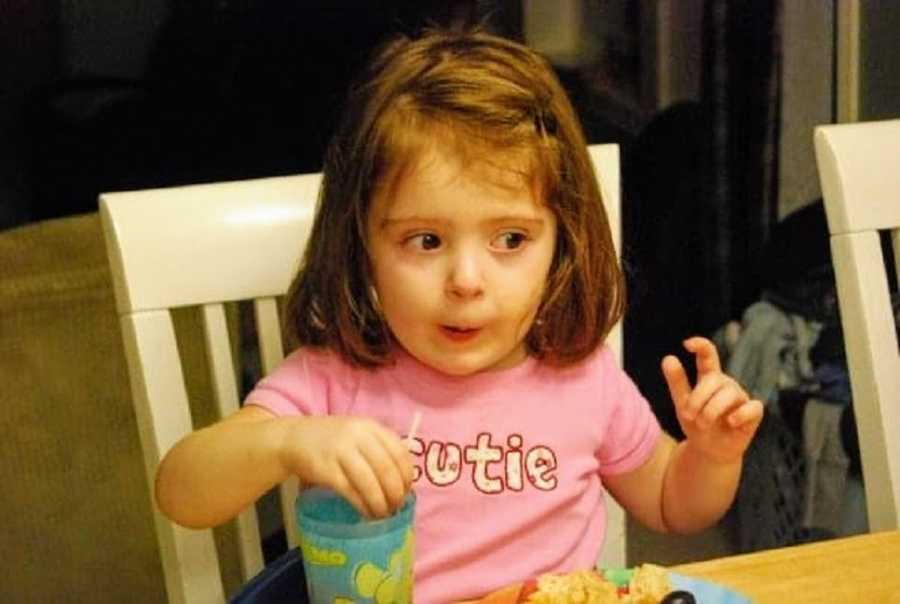 An adopted girl sits at a table to eat
