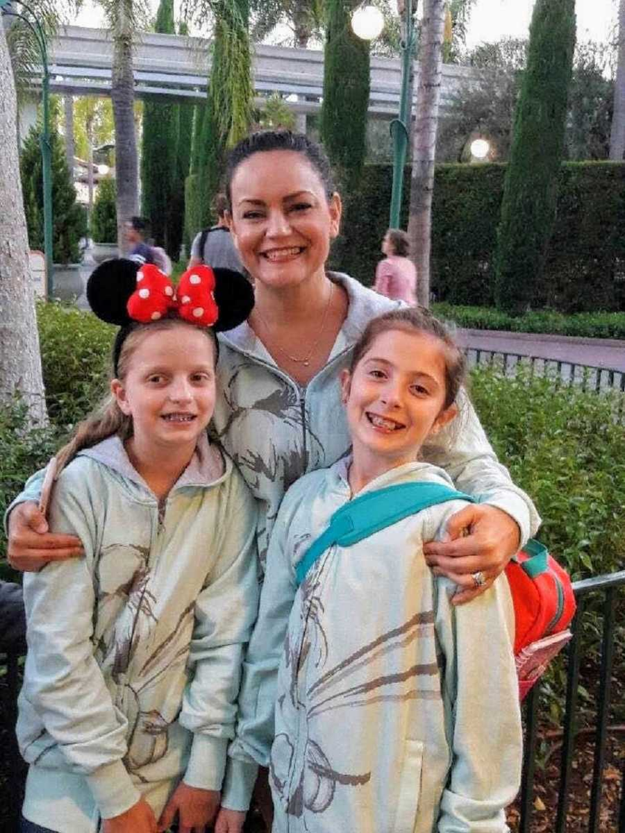 A mom stands with her adoptive daughters outsude