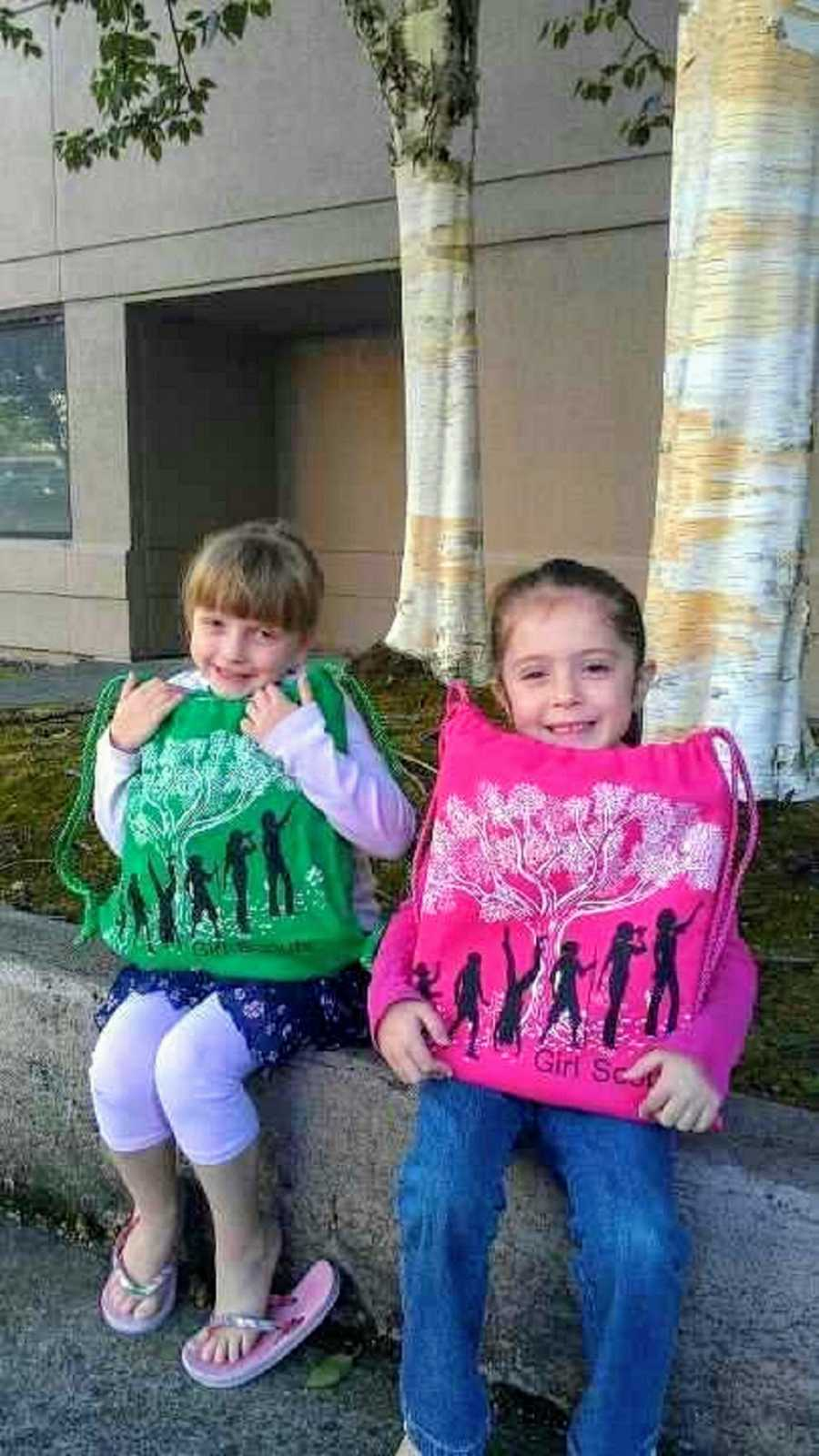 Adoptive sisters hold up pink and green bags