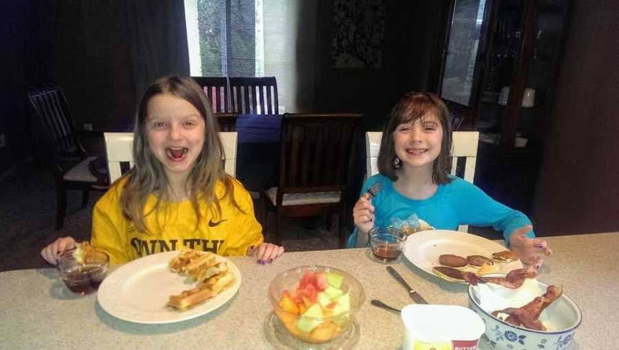 Adoptive sisters eat breakfast together at a counter