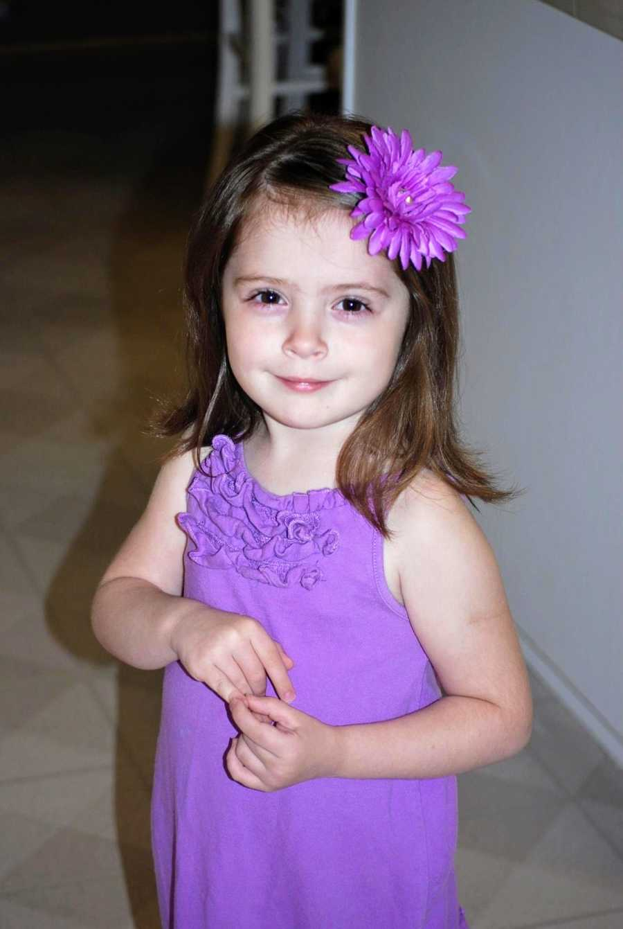 An adoptive girl wearing a purple dress
