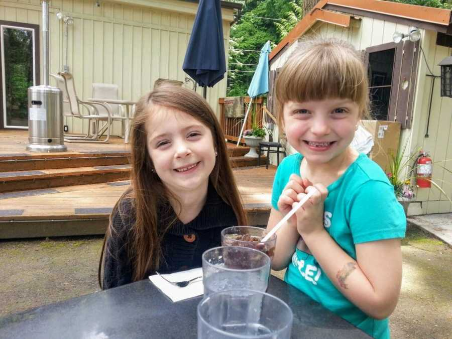 Adoptive sisters sit next to each other at a table