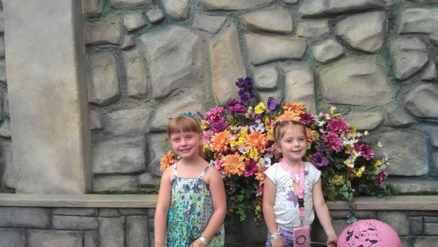Two adoptive sisters stand in front of flowers