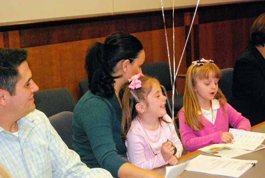 A mom sits with her daughters dressed in pink on adoption day