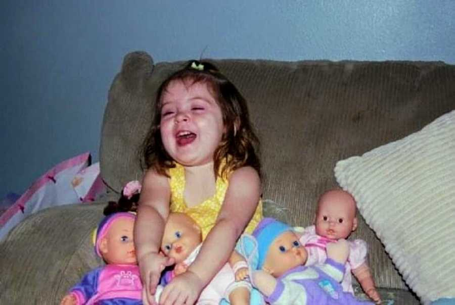 An adopted girl sits laughing with her dolls