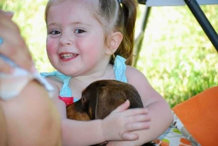An adoptive girl hugs a dog