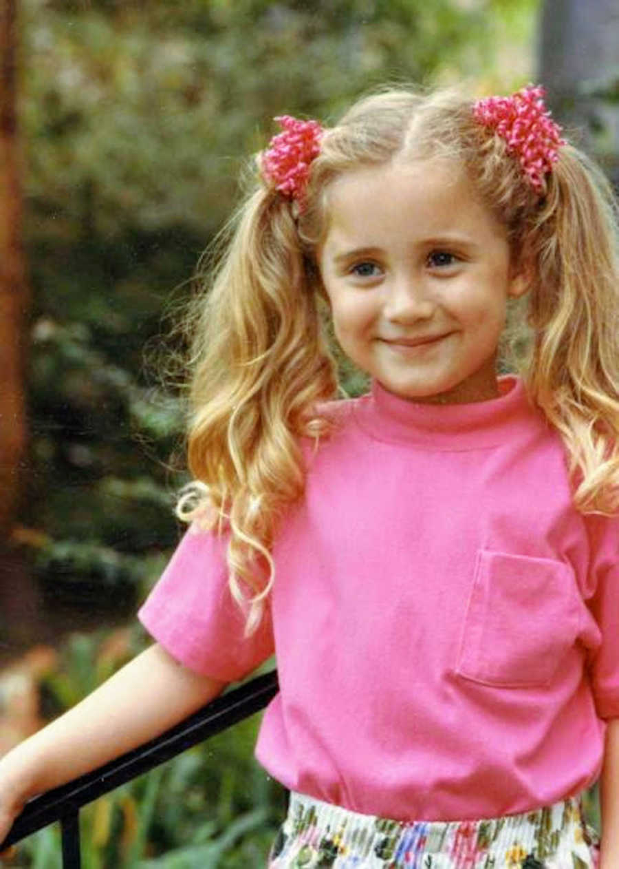 Young blonde girl with pigtails wearing pink shirt smiling outside