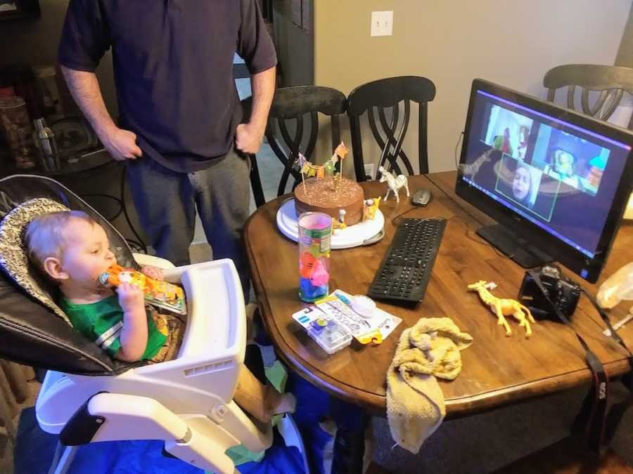 Baby boy sitting in high chair at first birthday video calling family