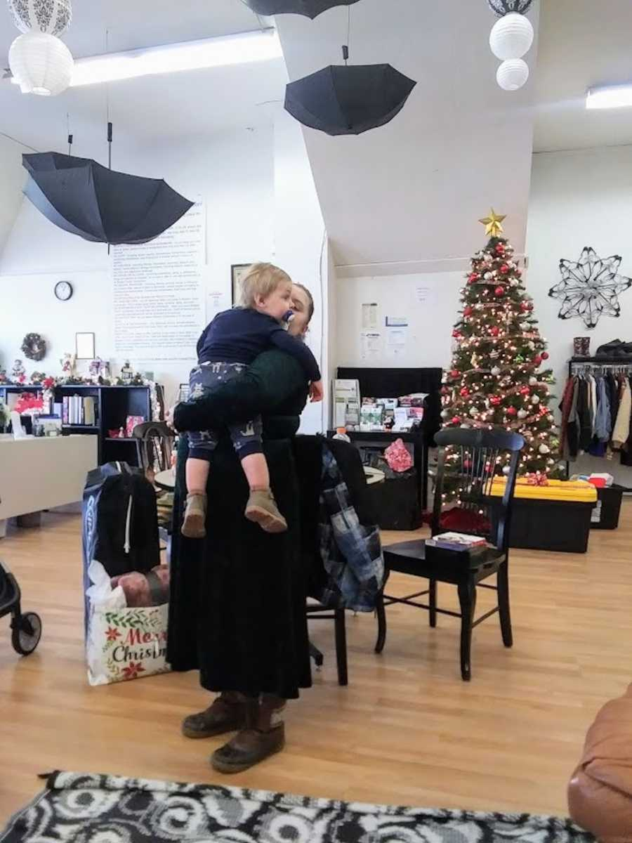 Birth mother holding her son at a community center with Christmas tree