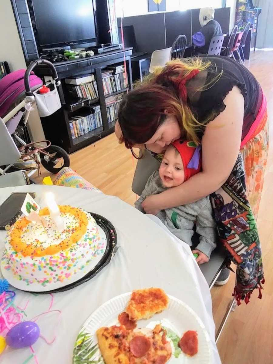Birth mother holding son at first birthday party with cake