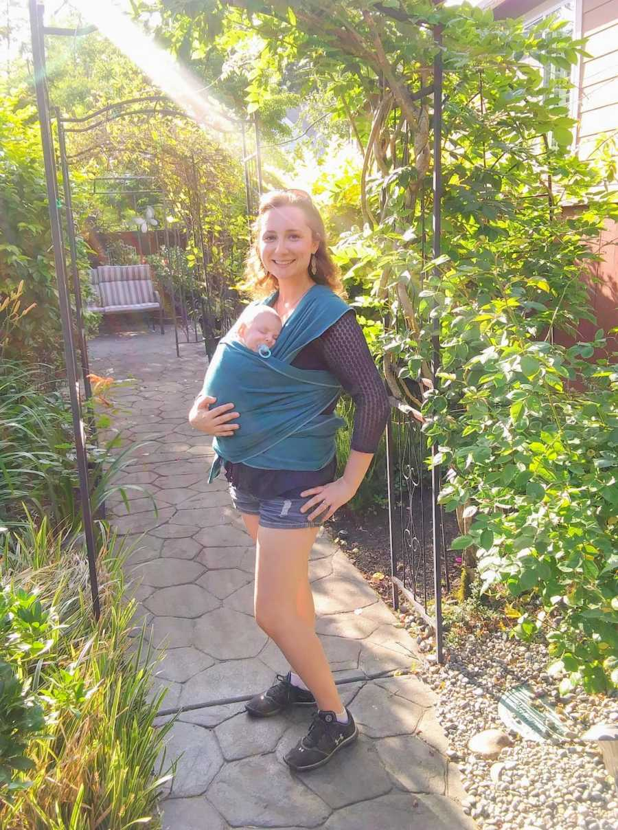 Mother standing outside wearing newborn son