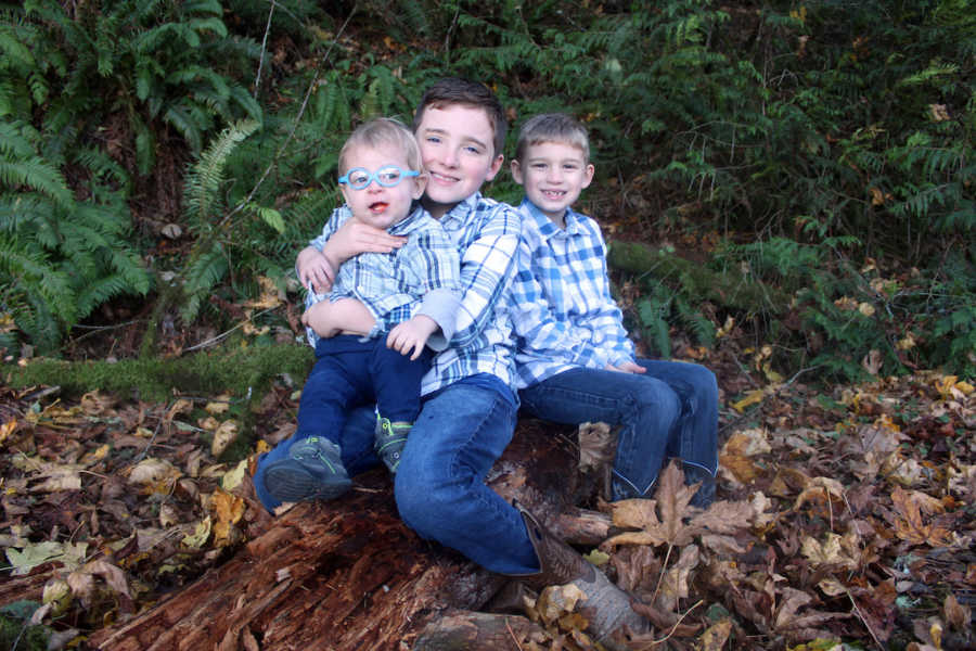 Three brothers sitting outside wearing blue shirts and smiling