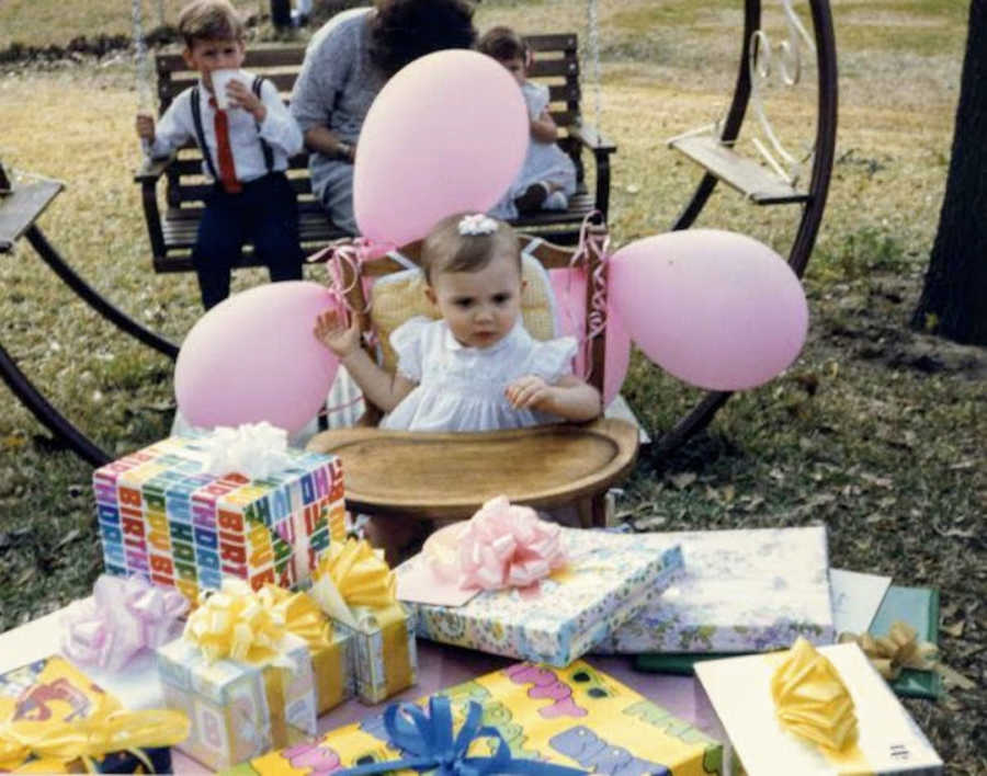 Baby girl in highchair with pink balloons at first birthday party with presents on a table