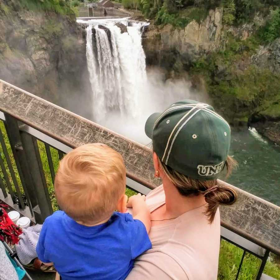 Mother and son standing at waterfall