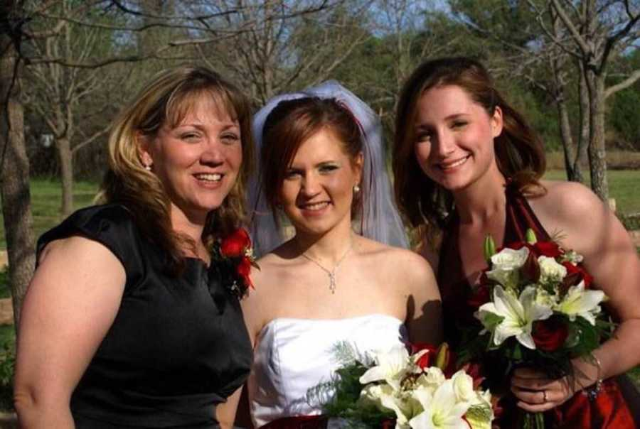Mother and daughters at wedding smiling outside with bride