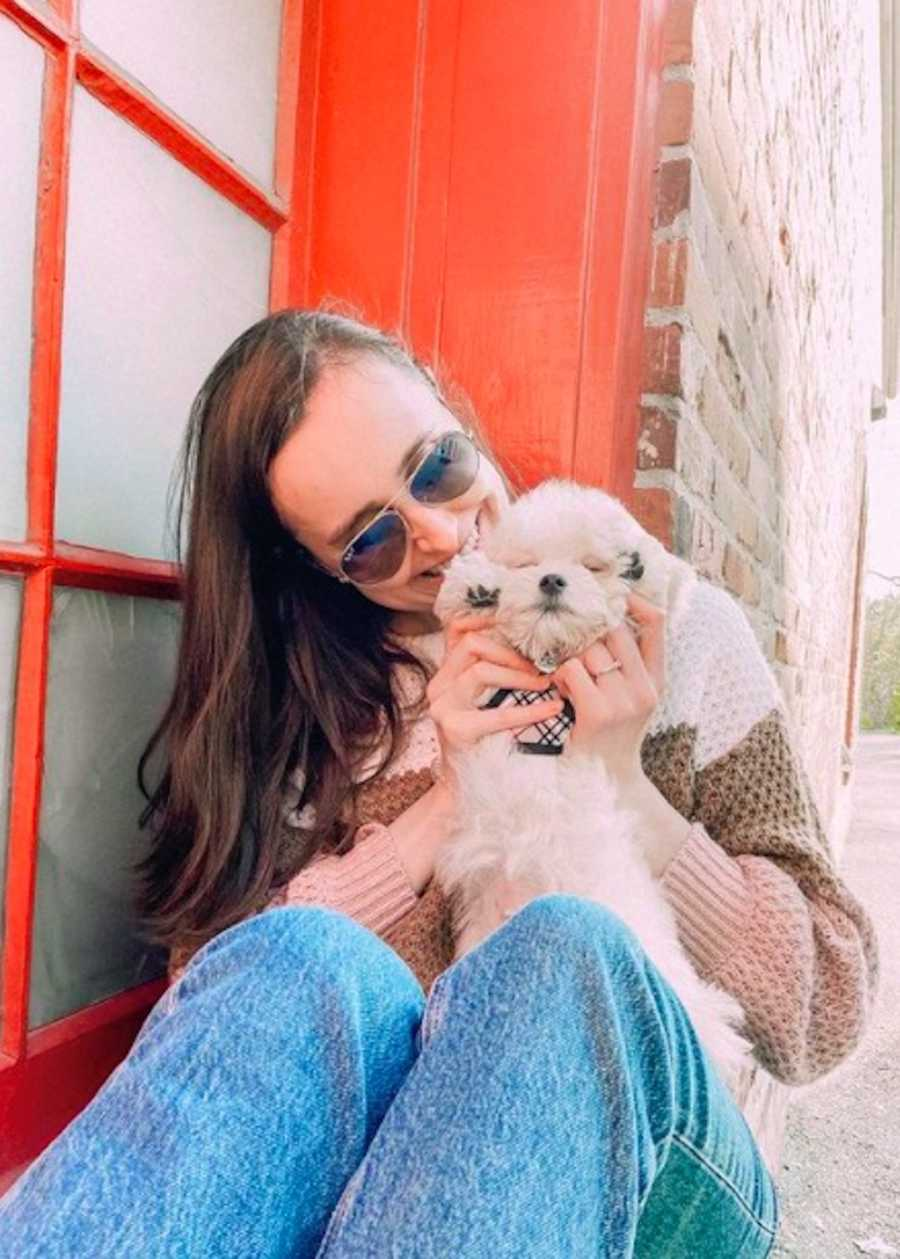 Young woman wearing sweater and sunglasses holding small white dog