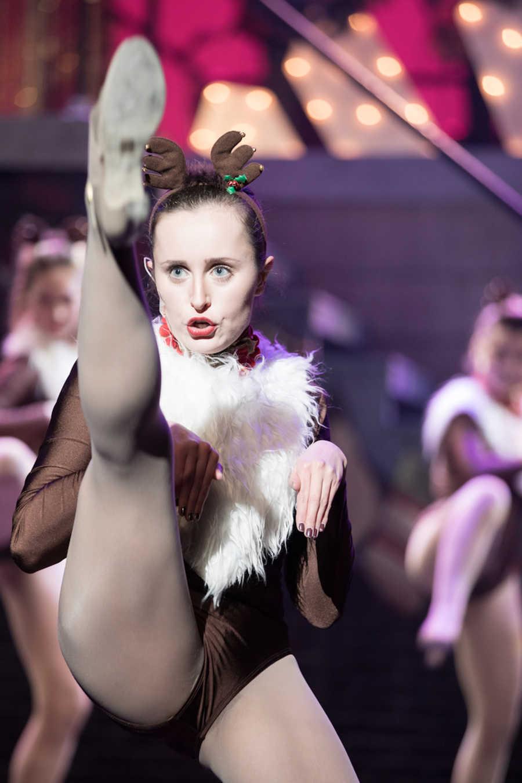Dancer wearing reindeer antlers kicking leg up in air