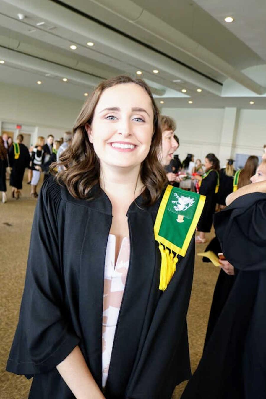 Young woman wearing graduation regalia smiling at camera
